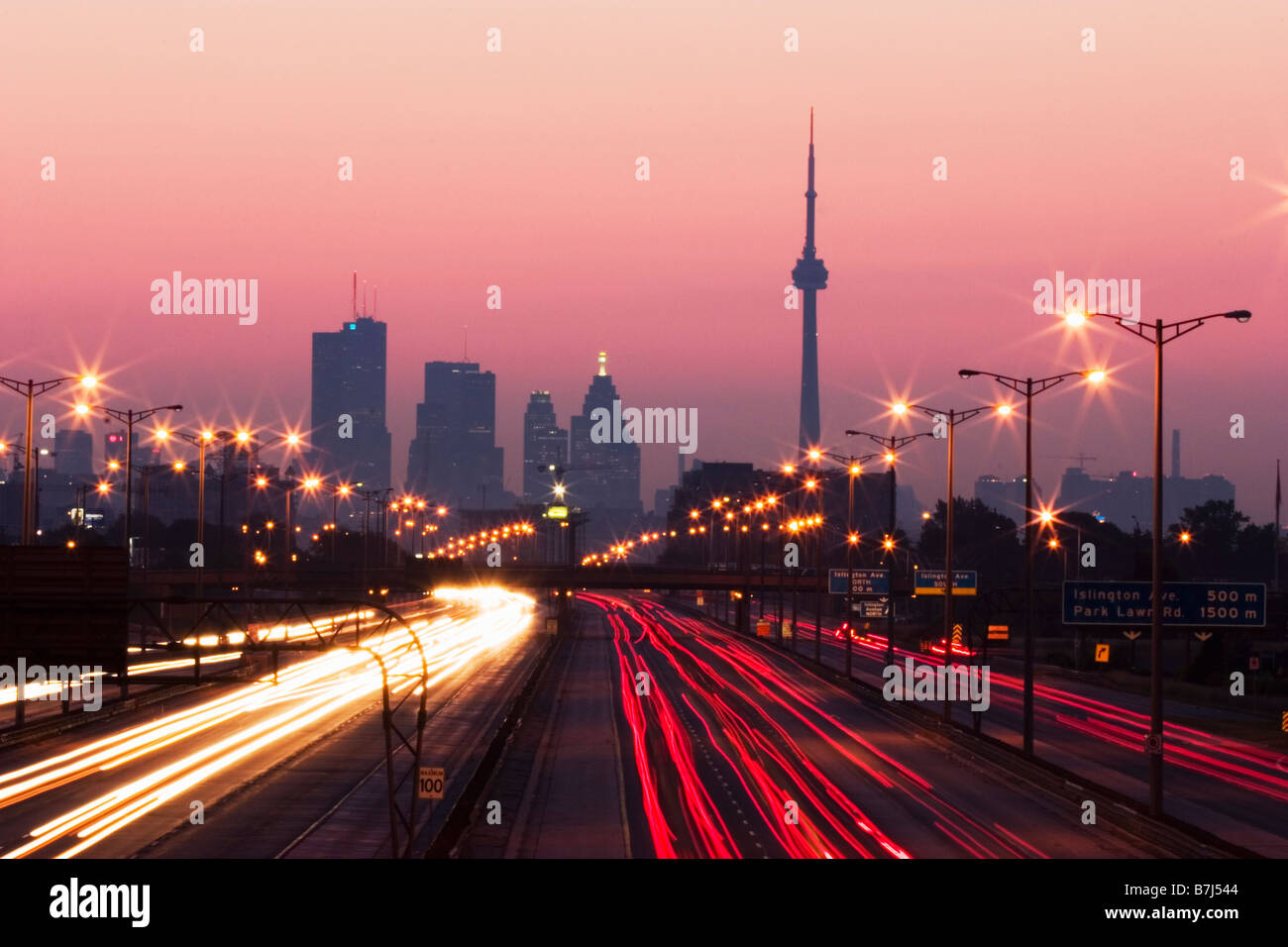 View of Toronto skyline from above Queen Elizabeth Way highway during start of rush hour traffic, Toronto, Ontario, - Stock Image