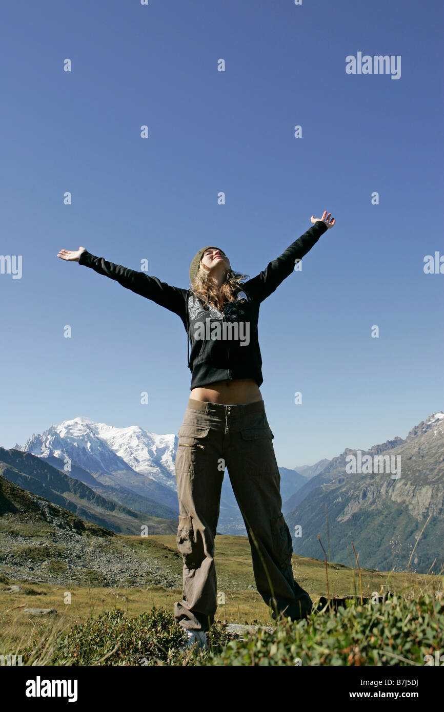 Young girl (19) arms stretched in front of Mont Blanc, Col de Balme Chamonix, France - Stock Image