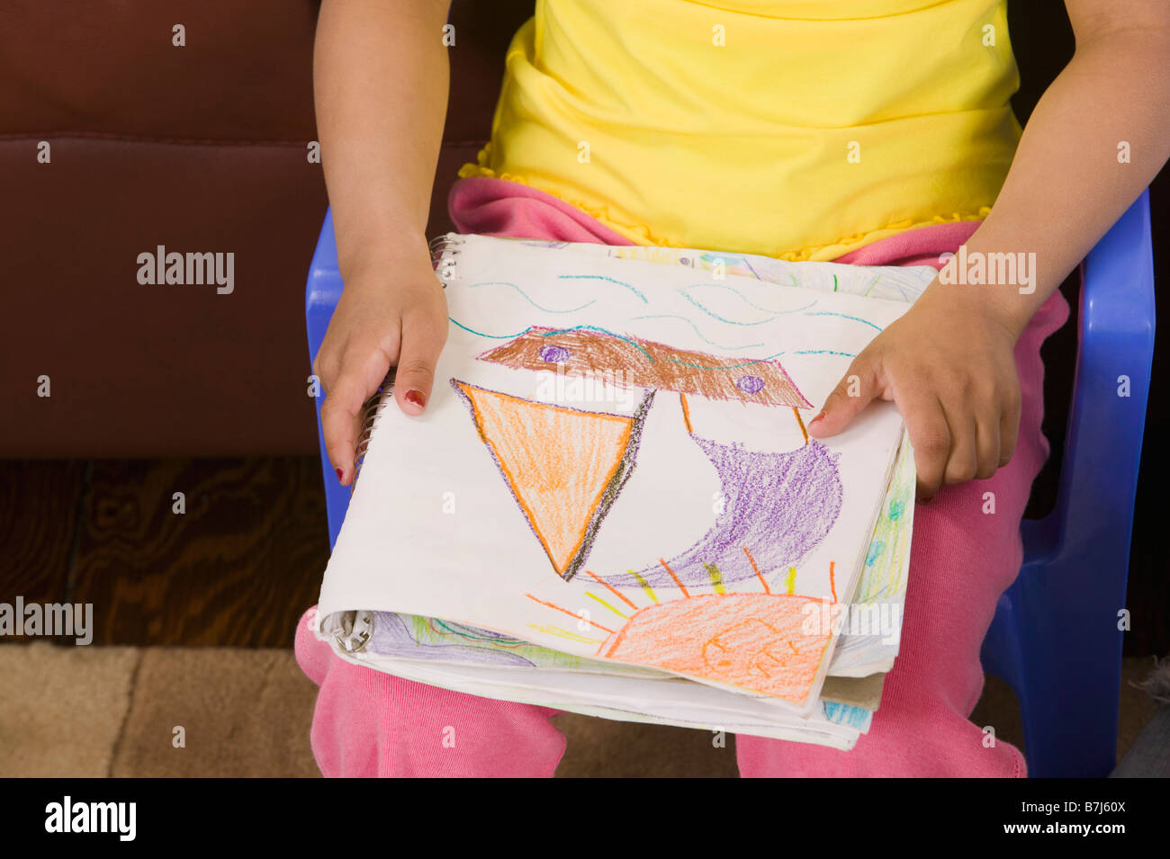 Mulatto girl 6 years old with her artwork. - Stock Image