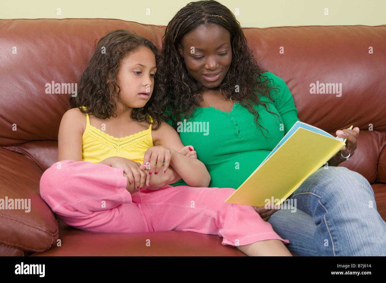 African American mom and Mulatto girl 6 years. Reading. - Stock Image