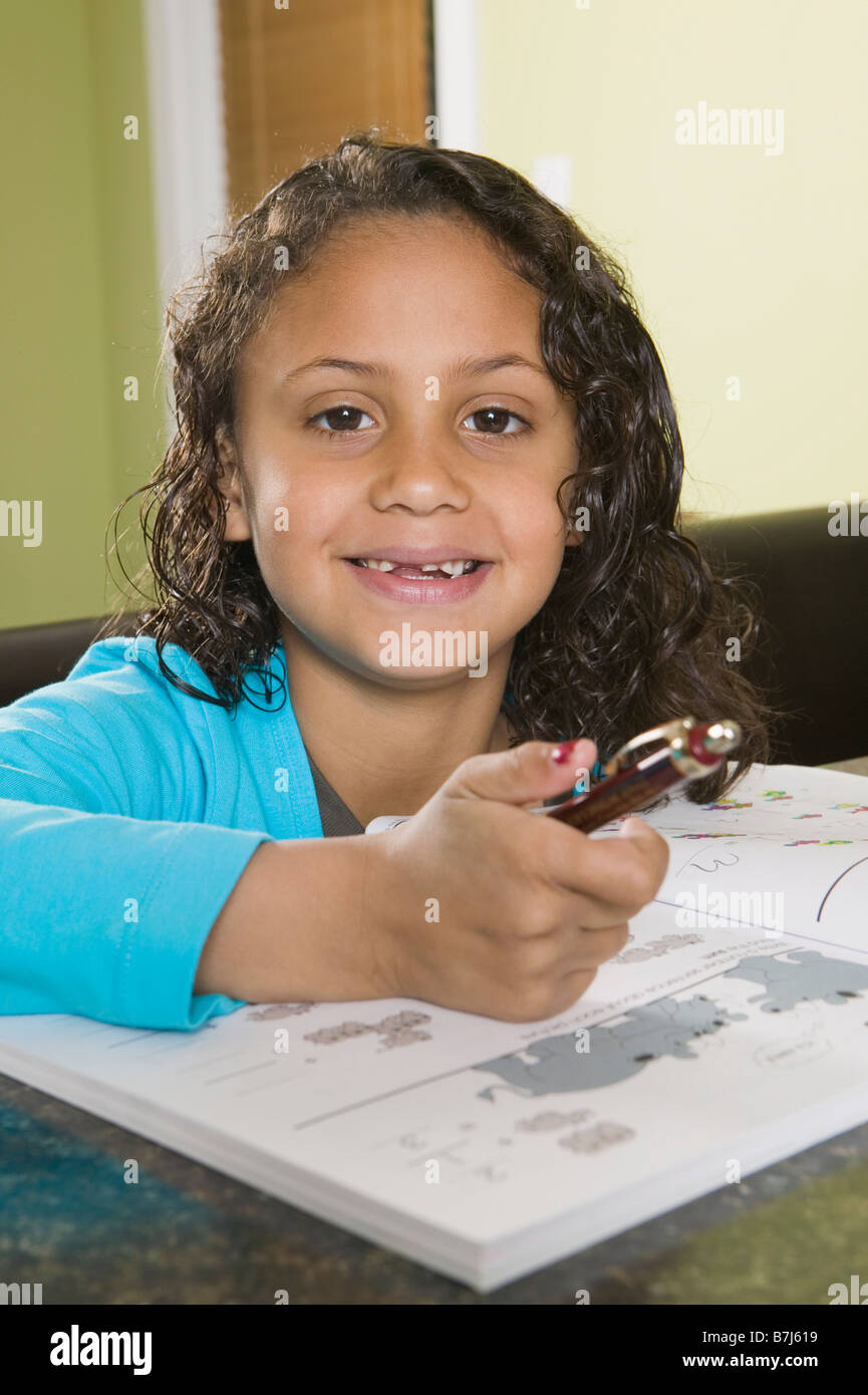 6 year old Mulatto girl practicing arithmetic. - Stock Image