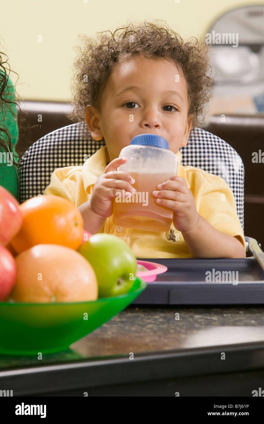 1.5 year old Mulatto boy drinking juice. - Stock Image