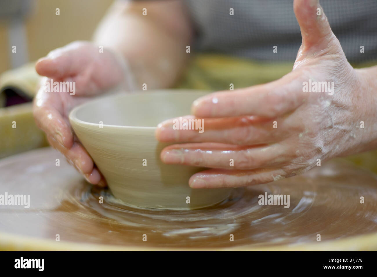 Hands molding a piece of pottery on a wheel-head, Burlington, Ontario Stock Photo