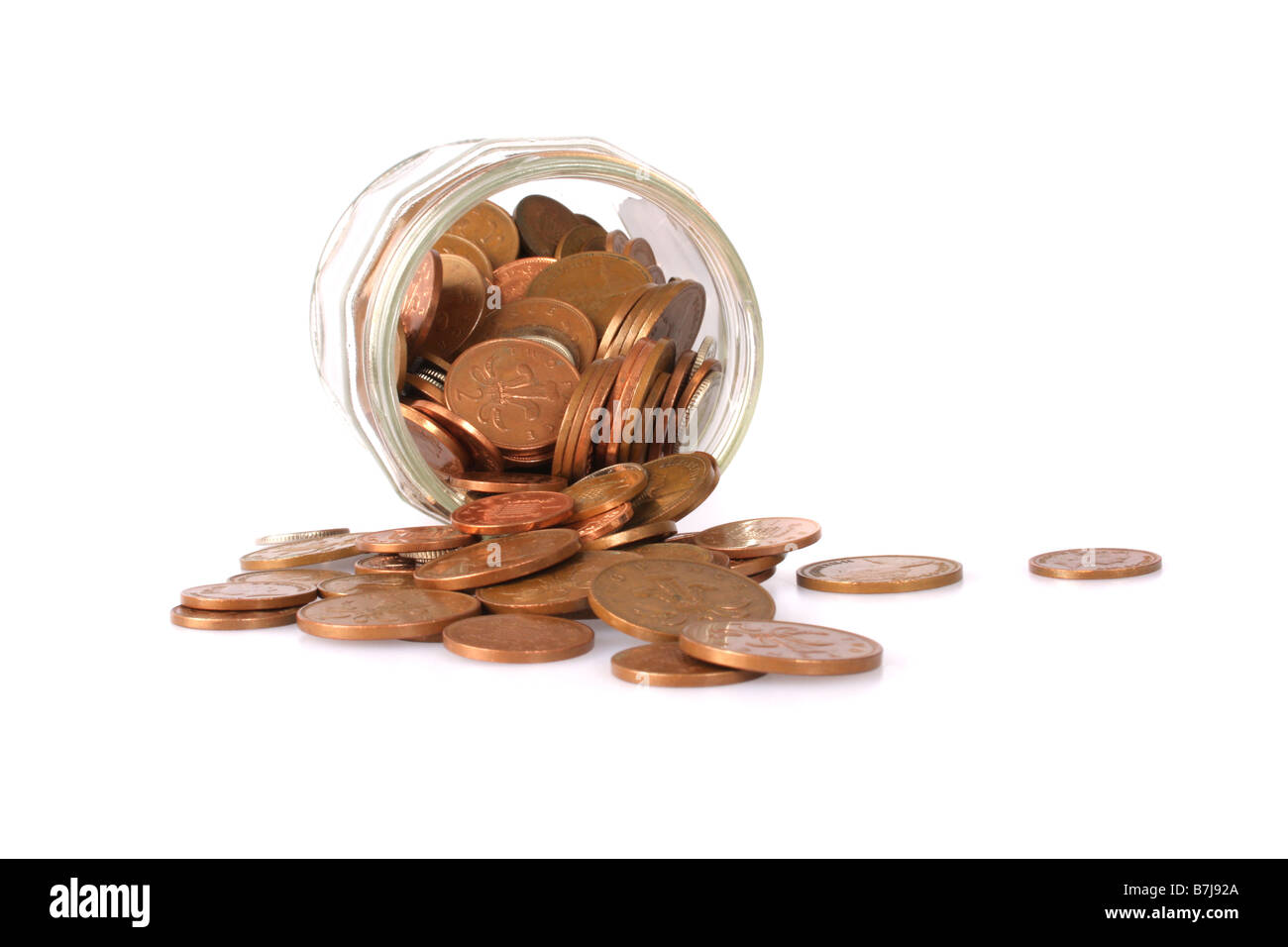 English coins spilling out of a jam jar. - Stock Image