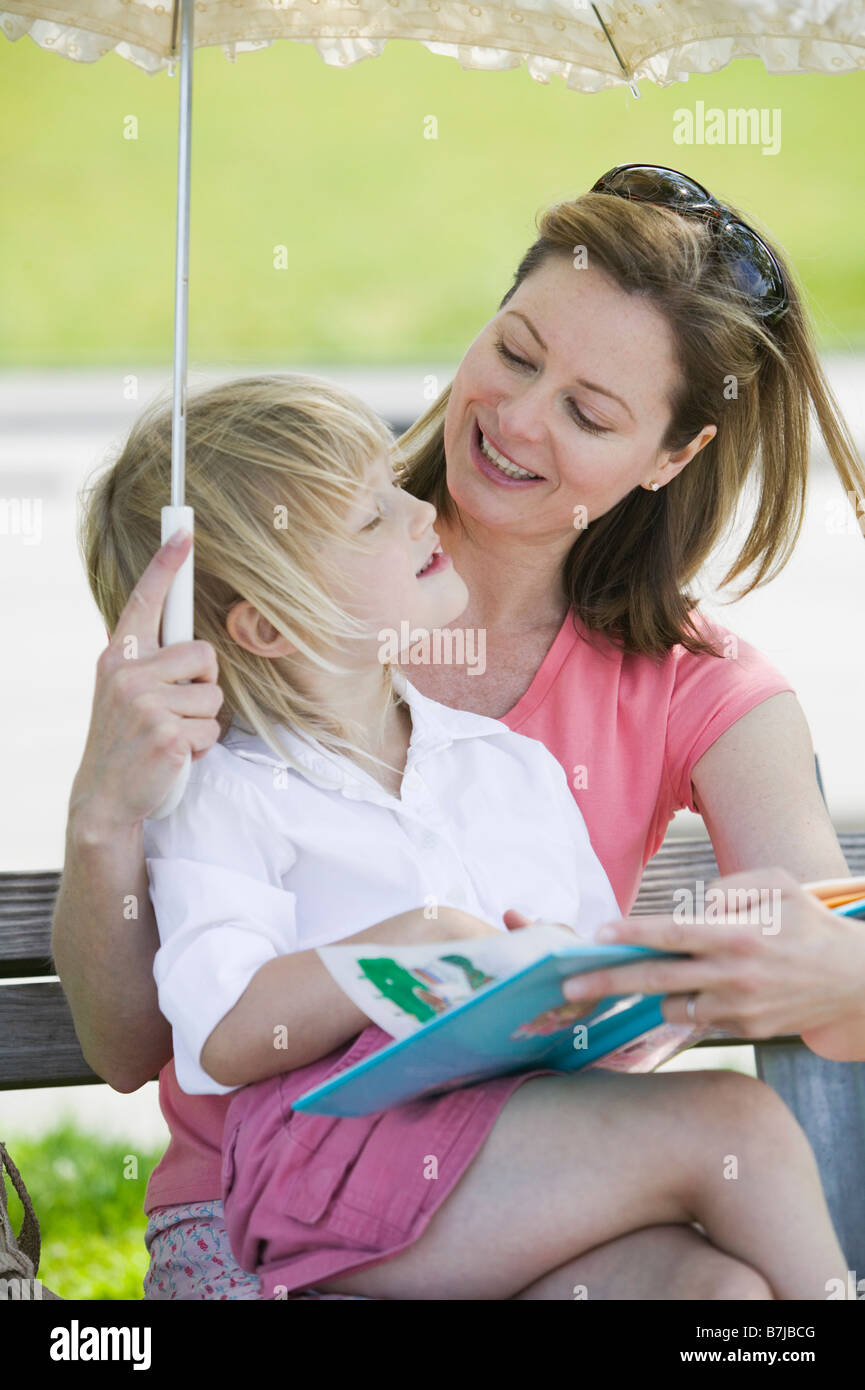 Caucasian Mom and 4 year old Daughter, reading a book on a park bench. Sunset Beach, Vancouver, BC - Stock Image