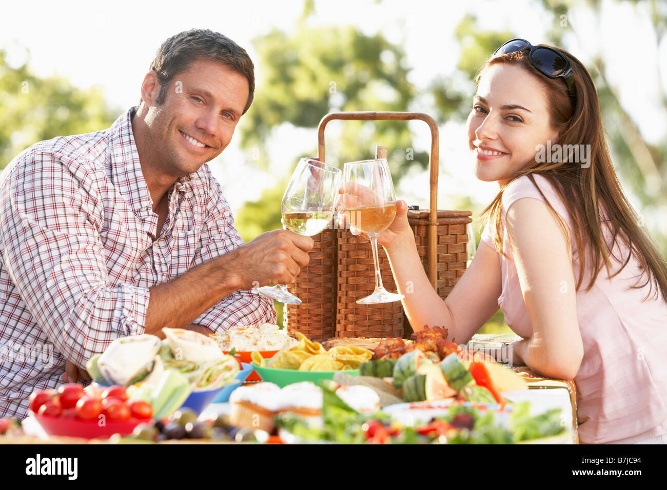 Couple Eating An Al Fresco Meal, Toasting With Wineglasses - Stock Image