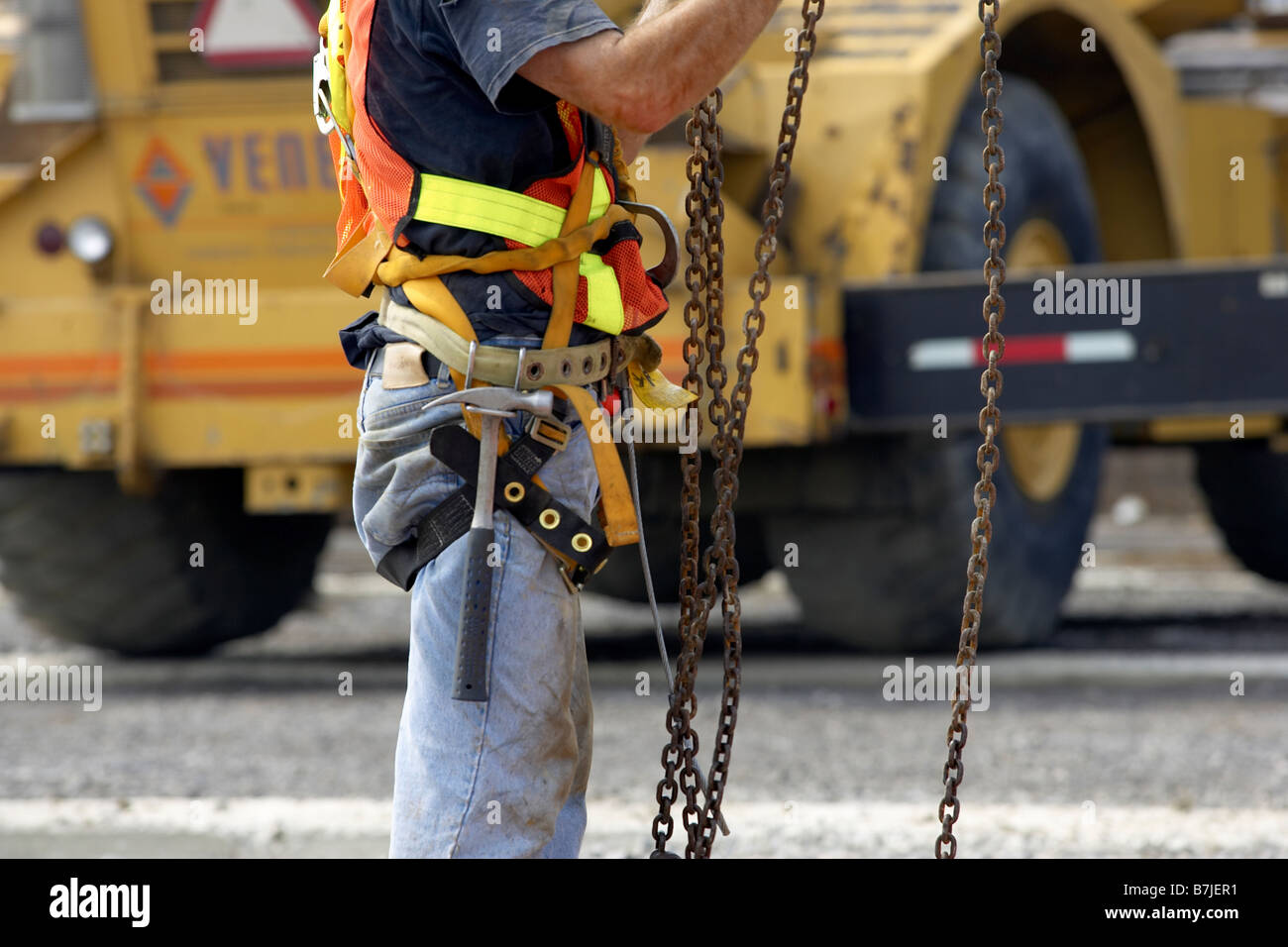 construction worker in harness and tool belt adjusting chains canada B7JER1 construction worker in harness and tool belt adjusting chains stock
