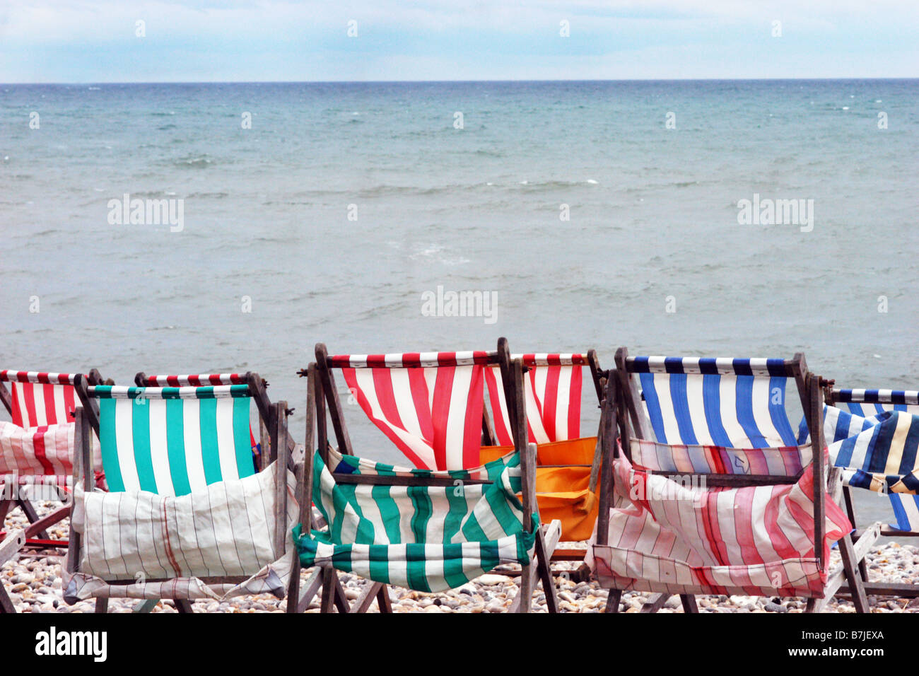 Battered deckchairs on a deserted beach, May Day Bank holiday Dorset UK - Stock Image