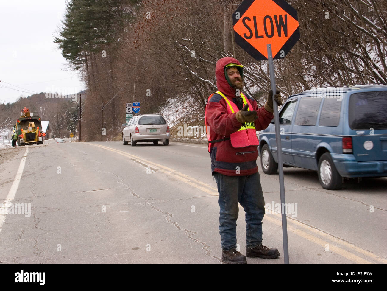 Flagger road worker holds traffic sign in middle of road - Stock Image