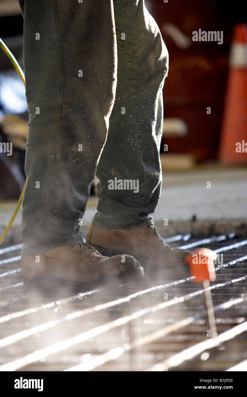 Worker walking on concrete form made of rebar; Canada, Ontario, Hamilton - Stock Image