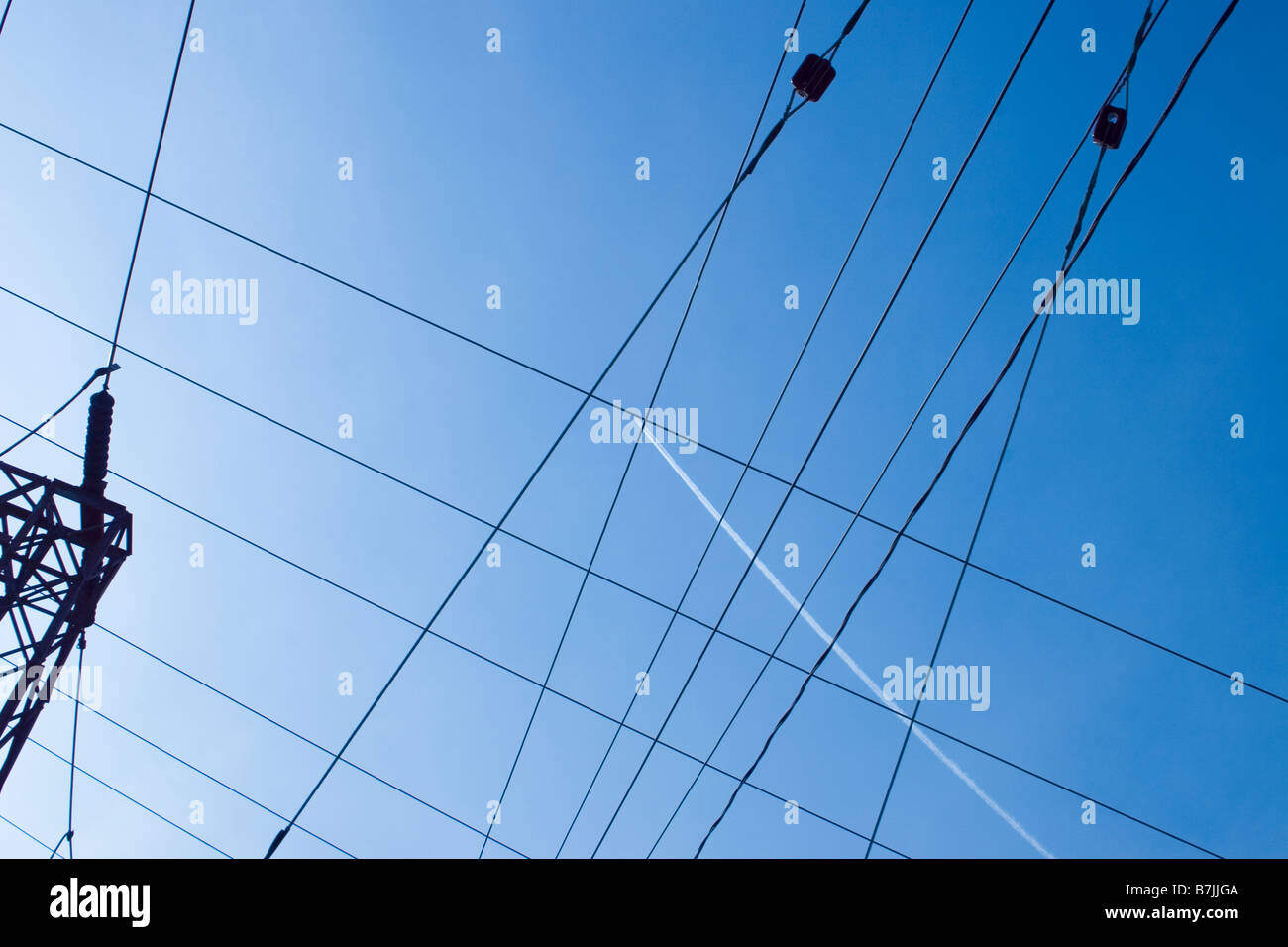 Jet contrail in midst of electric lines; Canada, Ontario - Stock Image