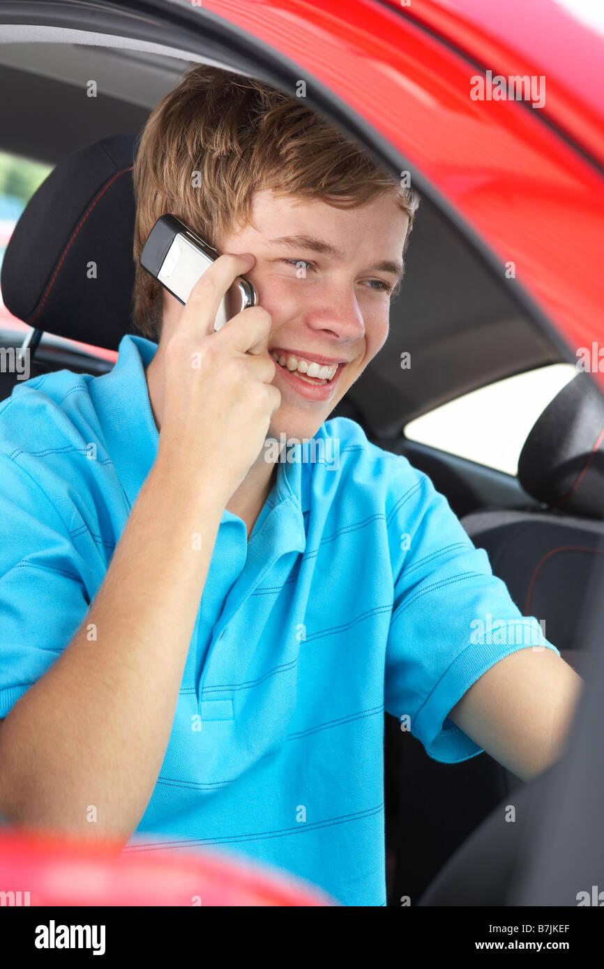 Teenage Boy Sitting In Car, Talking On Cellphone - Stock Image