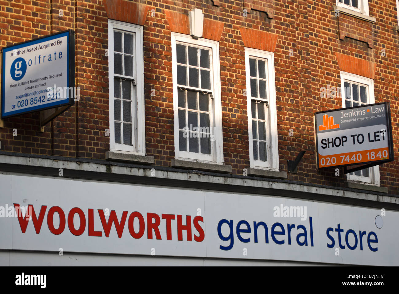 sign for woolworths general store beneath shop to let sign and a sign for the property company golfrate, in twickenham, - Stock Image
