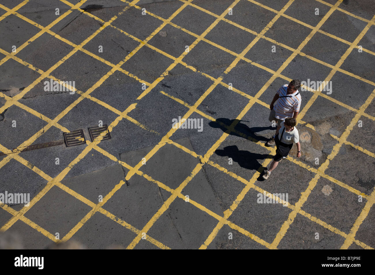 People walking across a road box junction - Stock Image