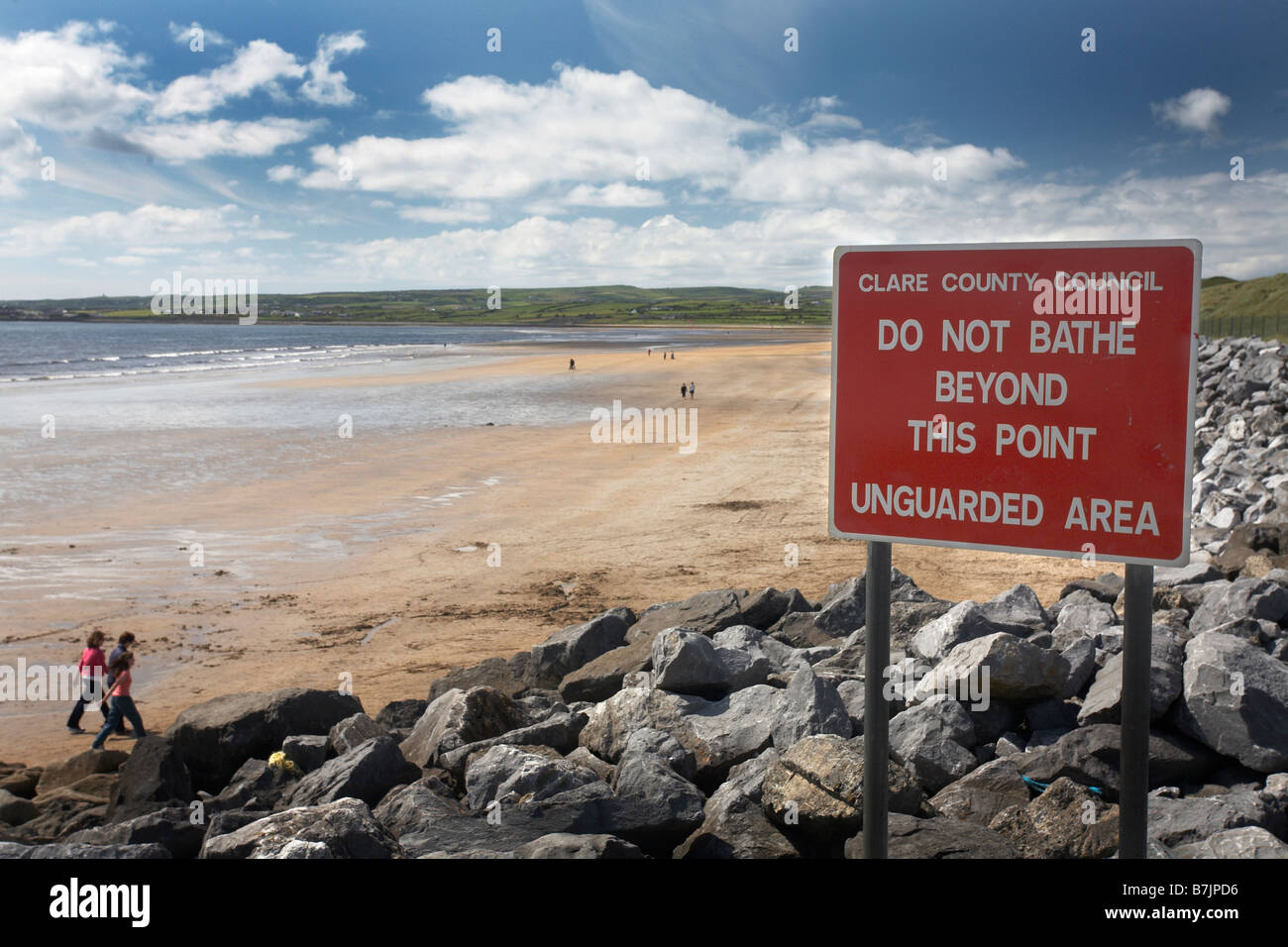 Warning sign on wall of rocks overlooking the beach. Low tide exposes wet sand and puddles of water from outgoing - Stock Image