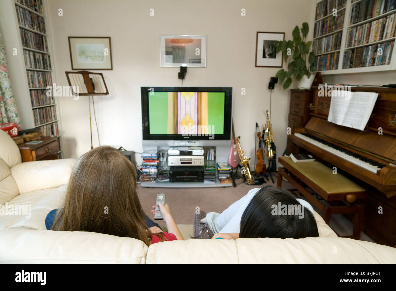 Two teenage girls watching a large TV, UK - Stock Image