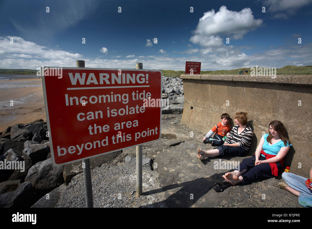 Family sitting in front of a warning sign. Leaned against a stone wall overlooking the beach. - Stock Image