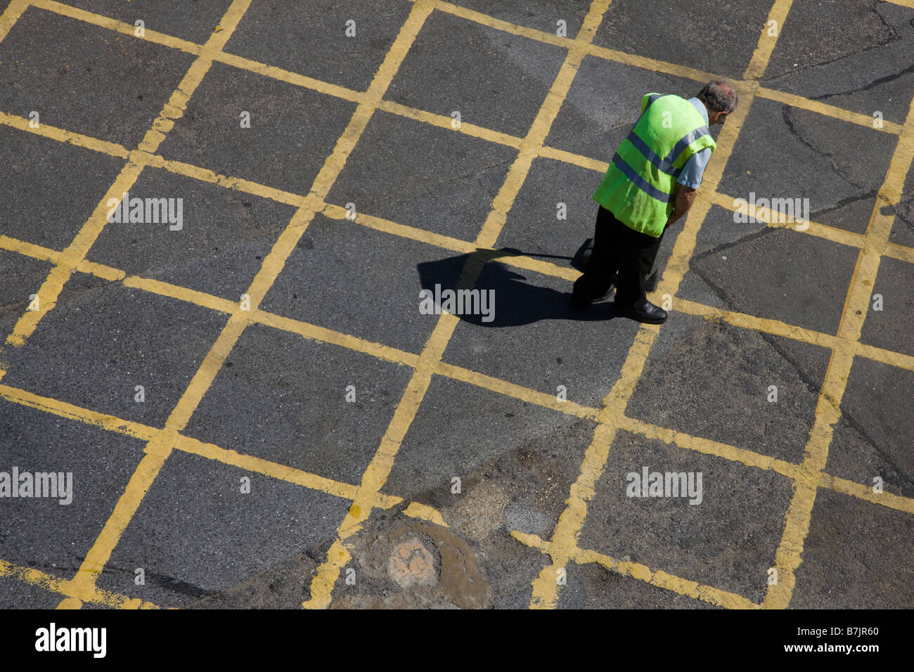 Man picking up litter in a road box junction - Stock Image
