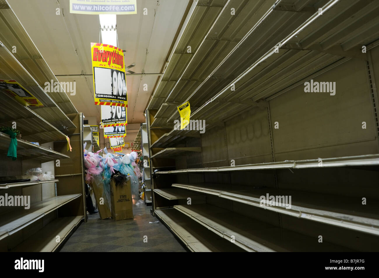 Empty shelves line the aisles on the last day of National Wholesale Liquidators' going out of business sale - Stock Image