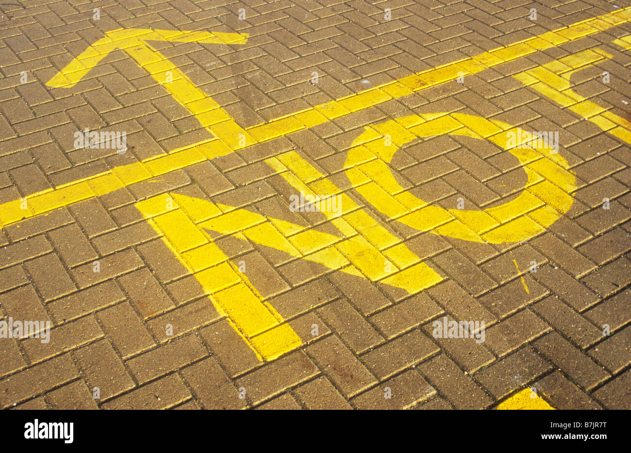Recently Painted Instruction In Yellow Paint On Brick Tile Road