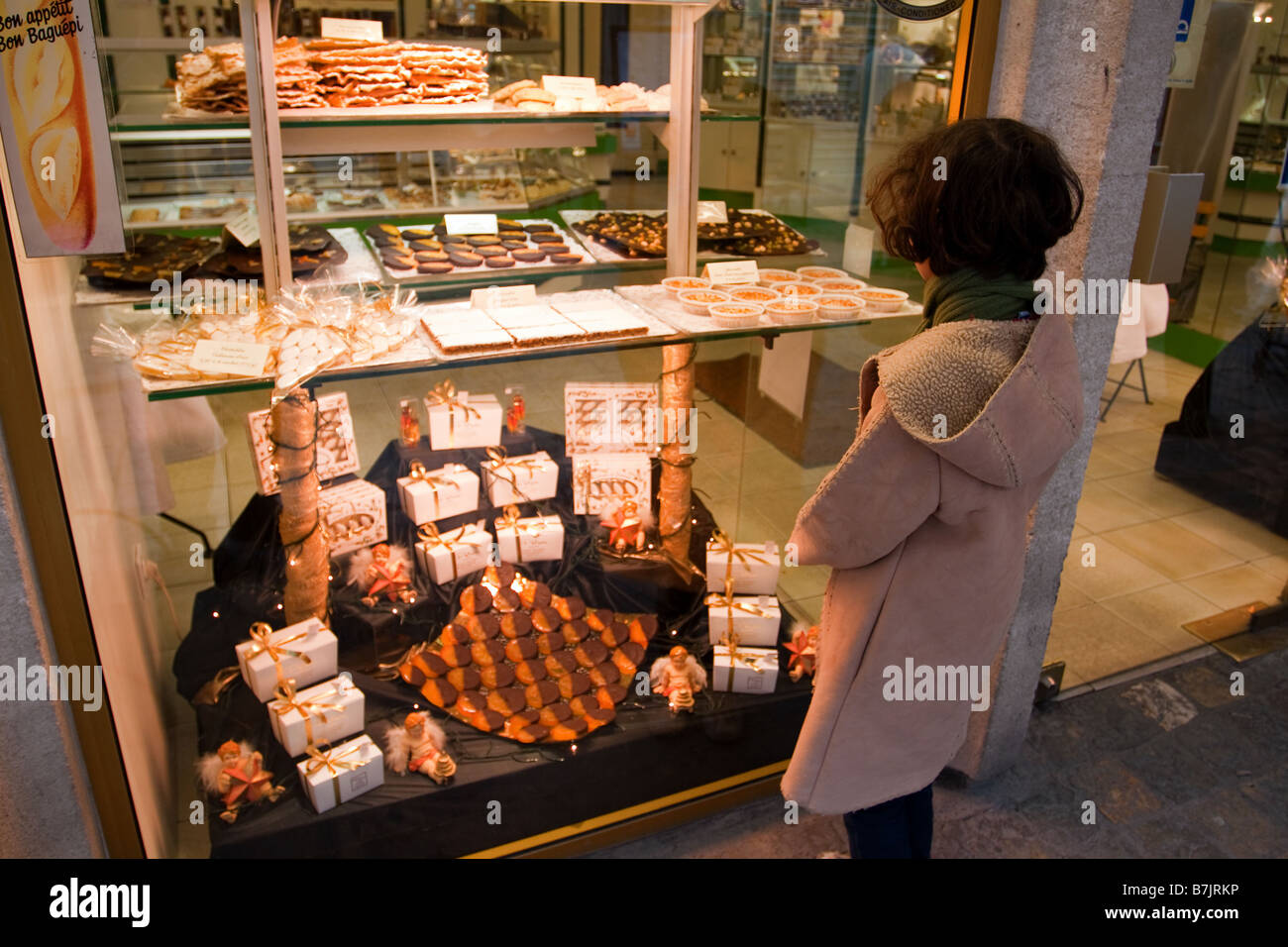 A young girl looks at a display of nougat  in a shop window in Aigues Mortes in Southern France - Stock Image