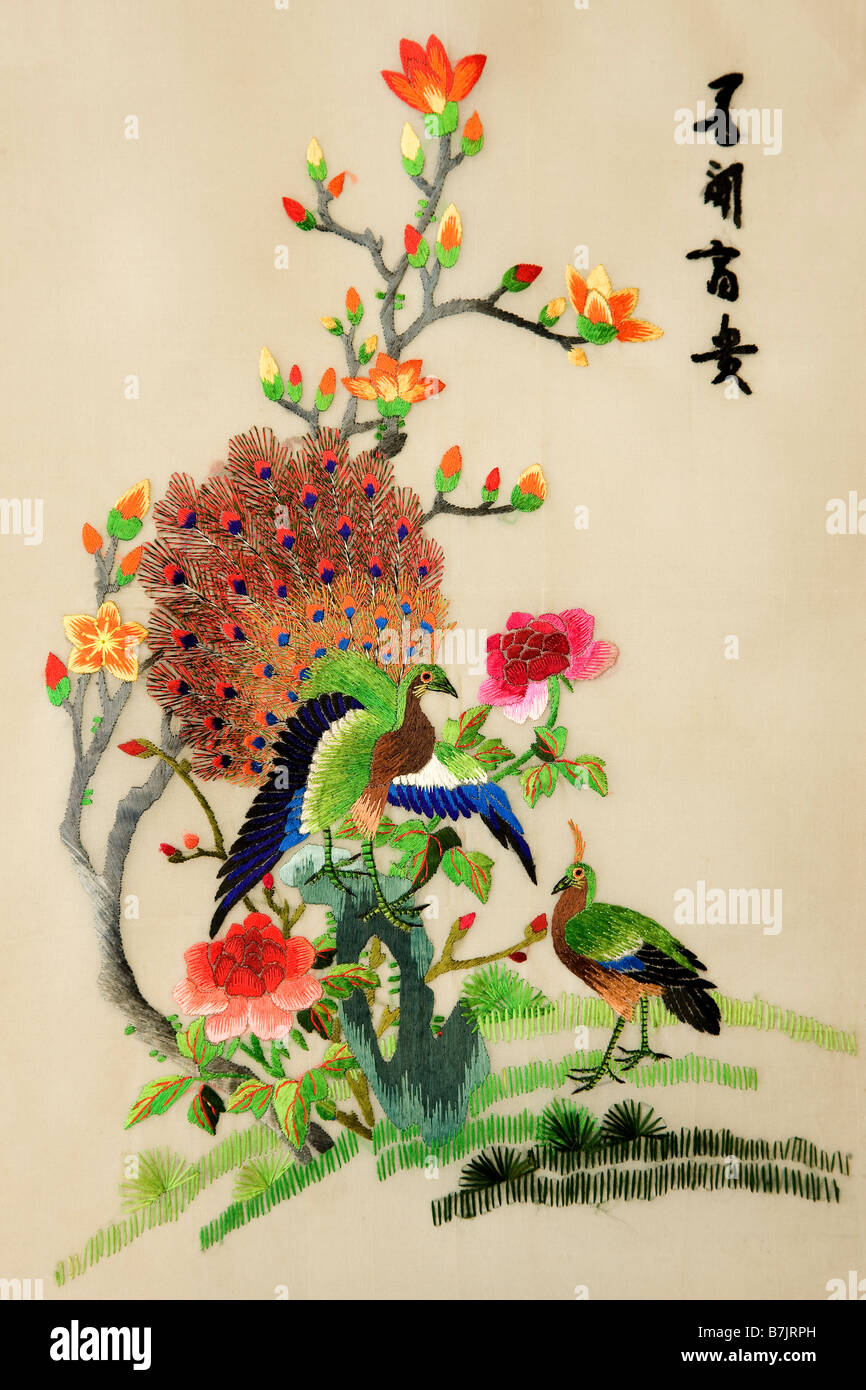 Colourful chinese silk embroidery of peacocks and bush in flower with text meaning 'Love to see wealth' - Stock Image