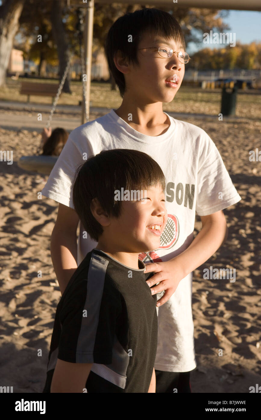 twelve year old japanese boy with hands on younger brother, looking towards the sunset outdoors - Stock Image