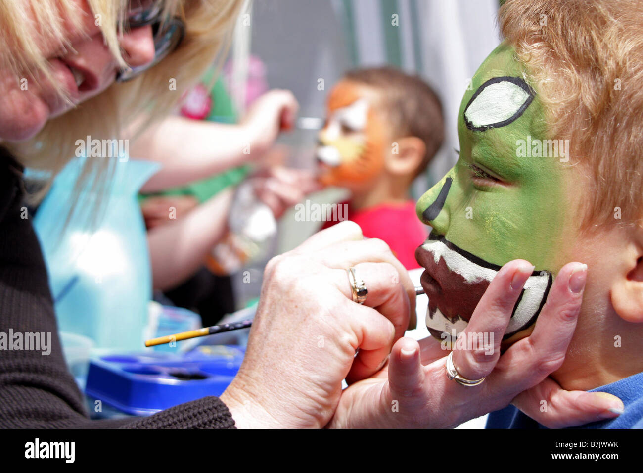 Young Children Having Faces Painted at a Fete in Oxfordshire 2008 - Stock Image