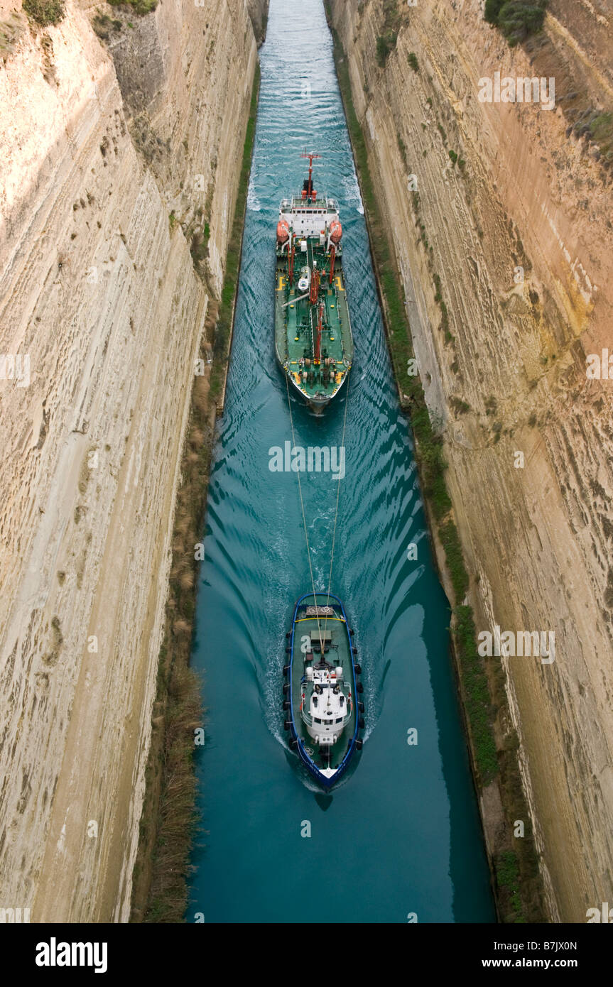 A tug pulls a fuel tanker through the Corinth Canal which jouns the gulf of Corinth with the Saronic Gulf Peloponnese - Stock Image