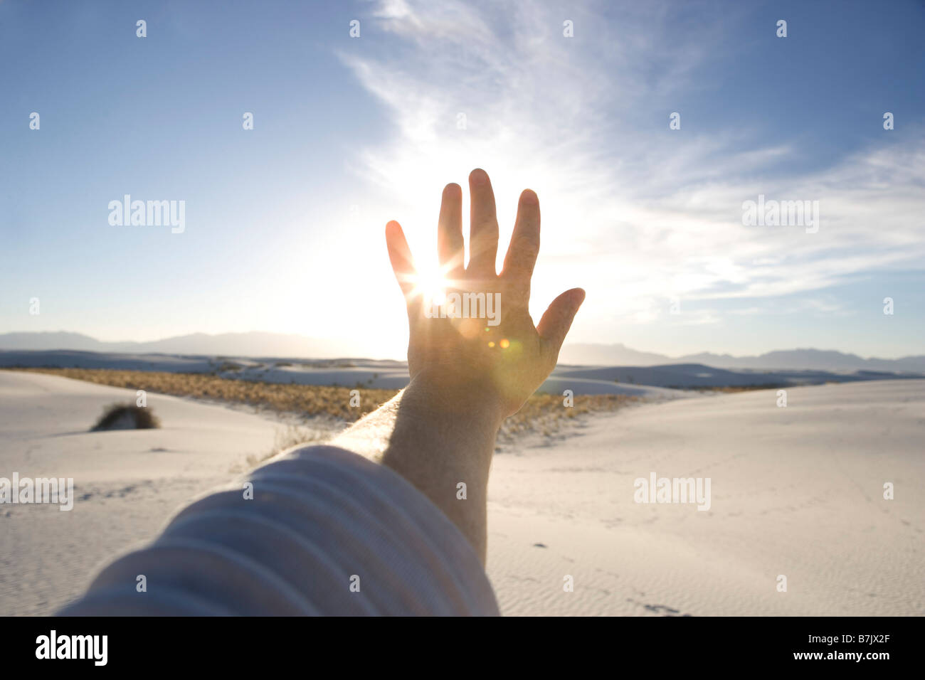 hand being held up to the sun with blue sky, sand dunes - Stock Image