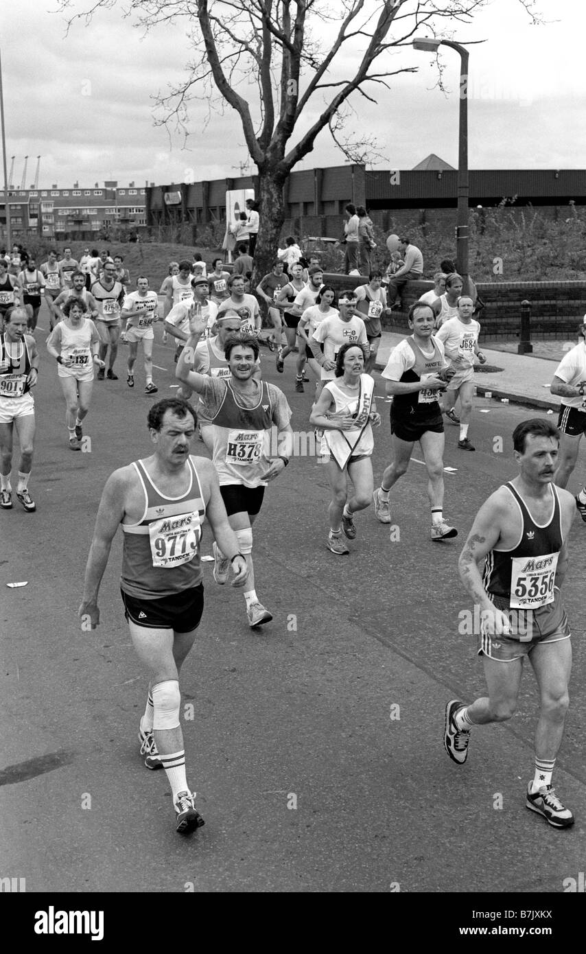 Runners in 1988 London Marathon with one waving and smiling. - Stock Image