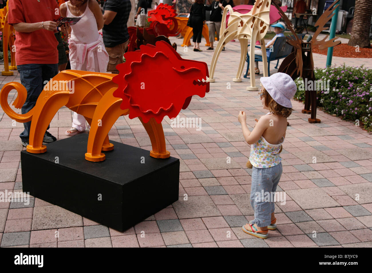 Young girl 4-6 years old is curious and fascinated by a sculpture of a metal lion. - Stock Image