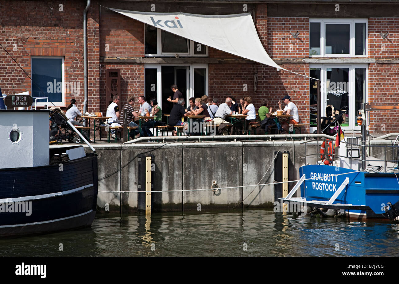 People eating outdoors at cafe on wharf Wismar harbour Germany - Stock Image