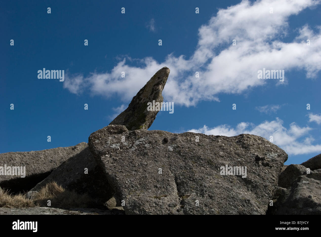 Piece of granite pointing to a blue sky with white clouds - Stock Image