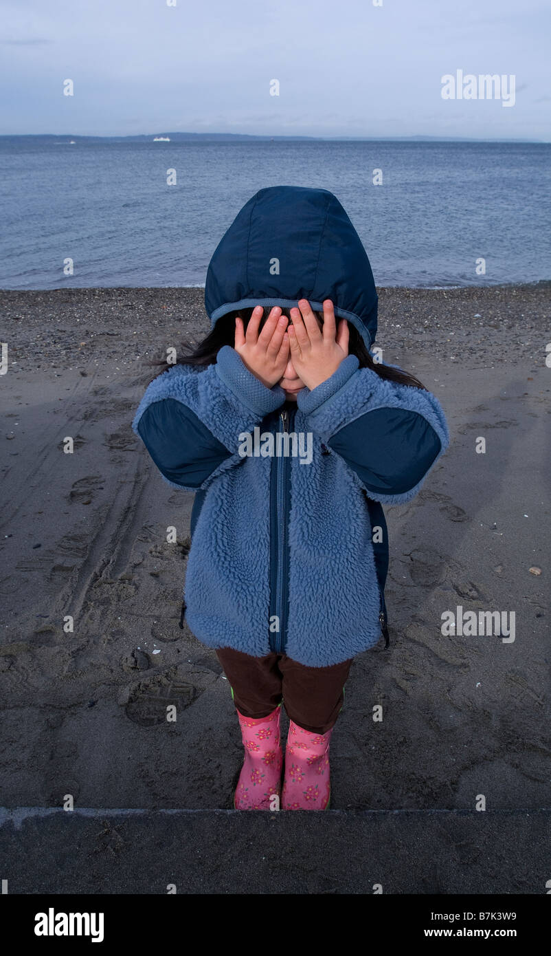 Girl covering her eyes with body of water in the background. - Stock Image