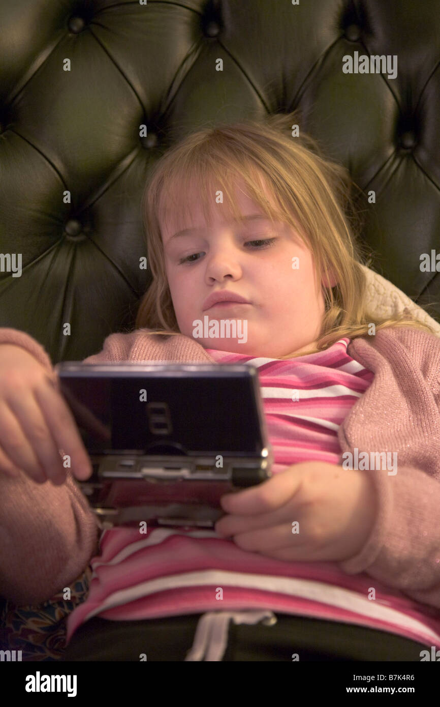 5 year old girl playing Nintendo ds Lite console - Stock Image
