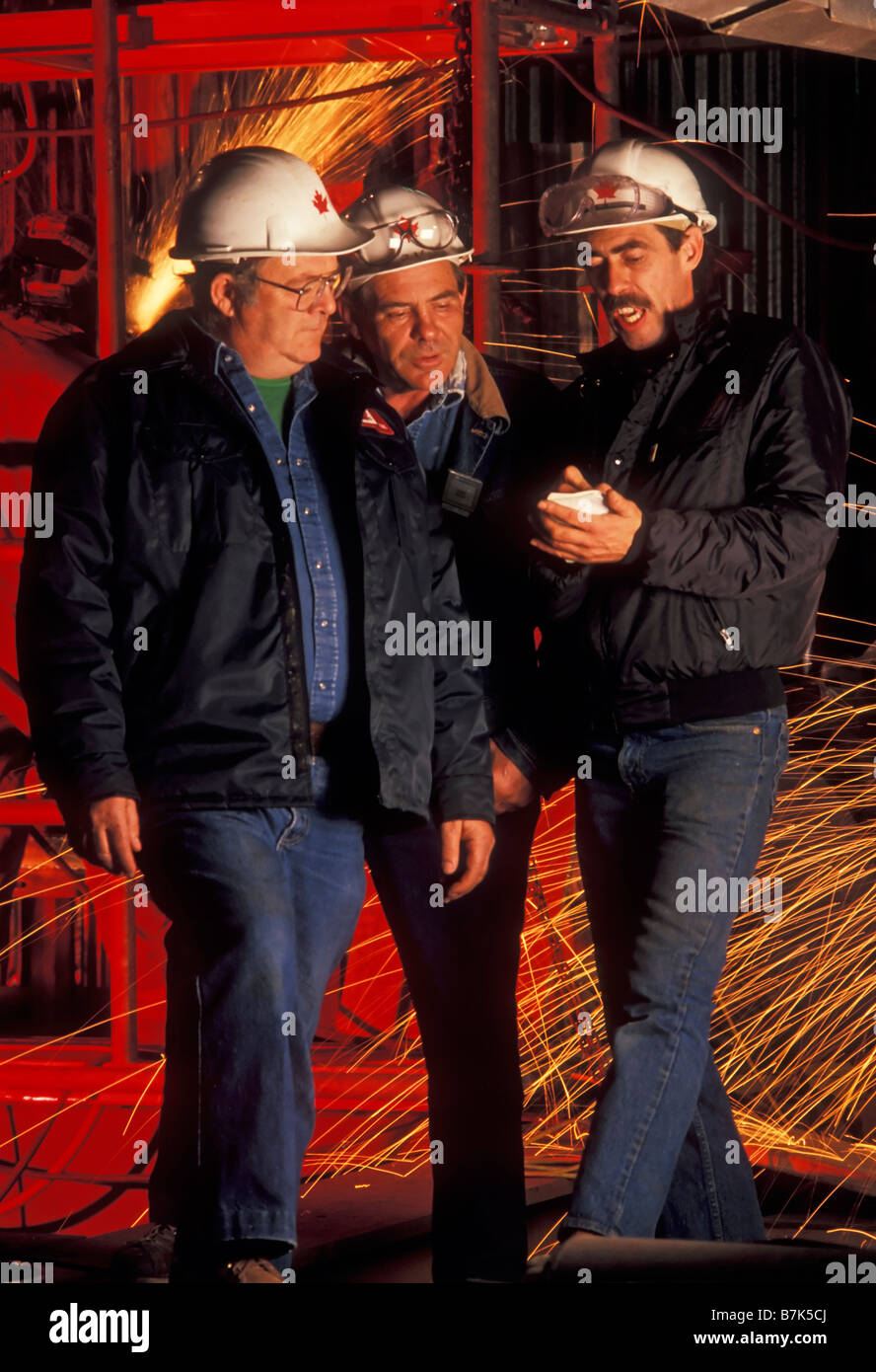 Project supervisors discussing pulp mill re fit with welding sparks in background, British Columbia, Canada. - Stock Image