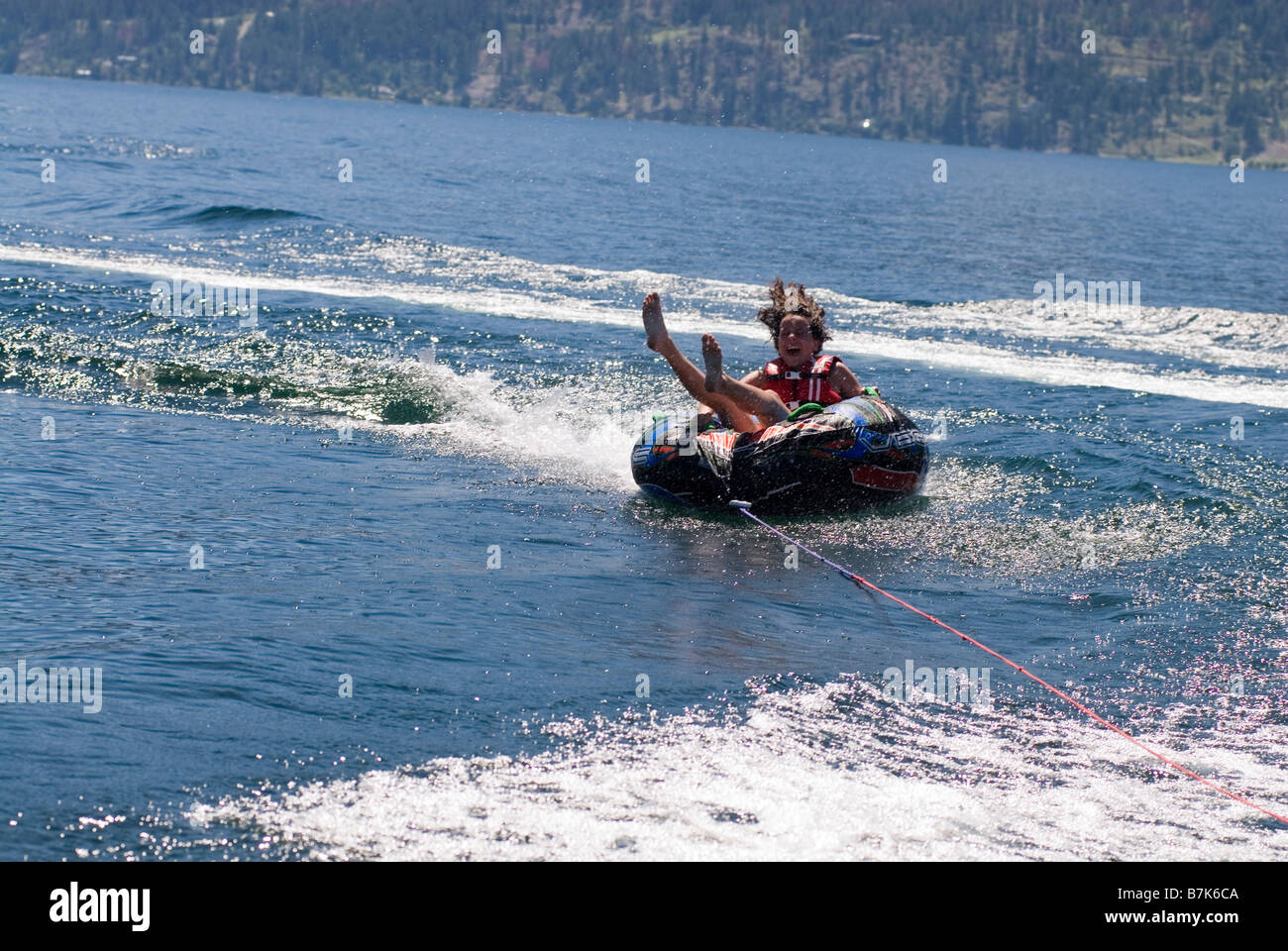 Young woman on inner tube behind boat, Okanagan Centre, BC Canada - Stock Image