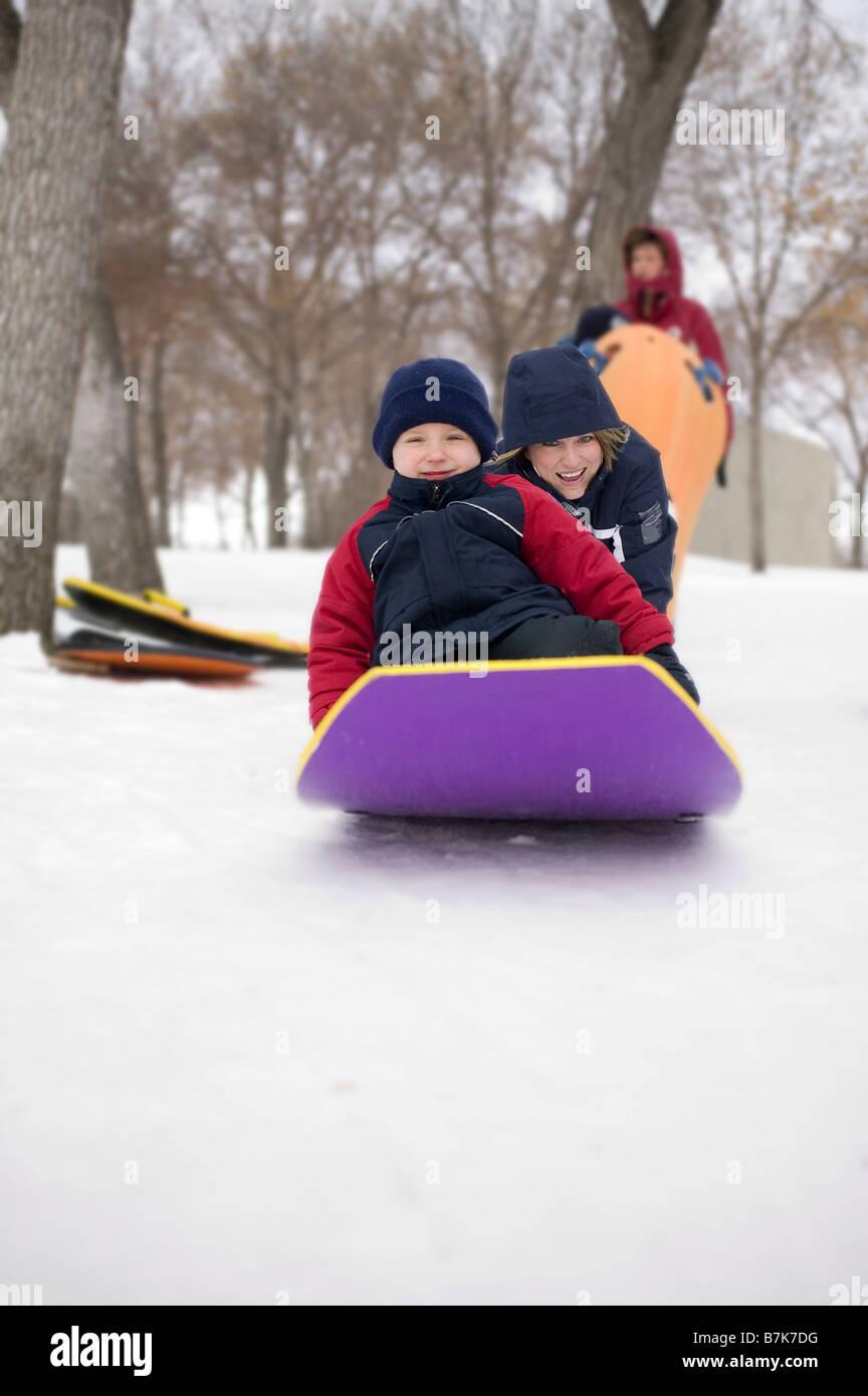 Gril pushes another child on toboggan, Regina, Saskatchewan, Canada - Stock Image