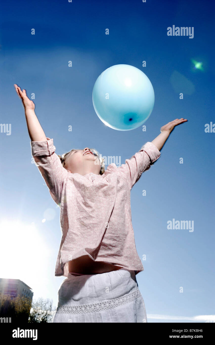 3 years old girl throwing a balloon - Stock Image