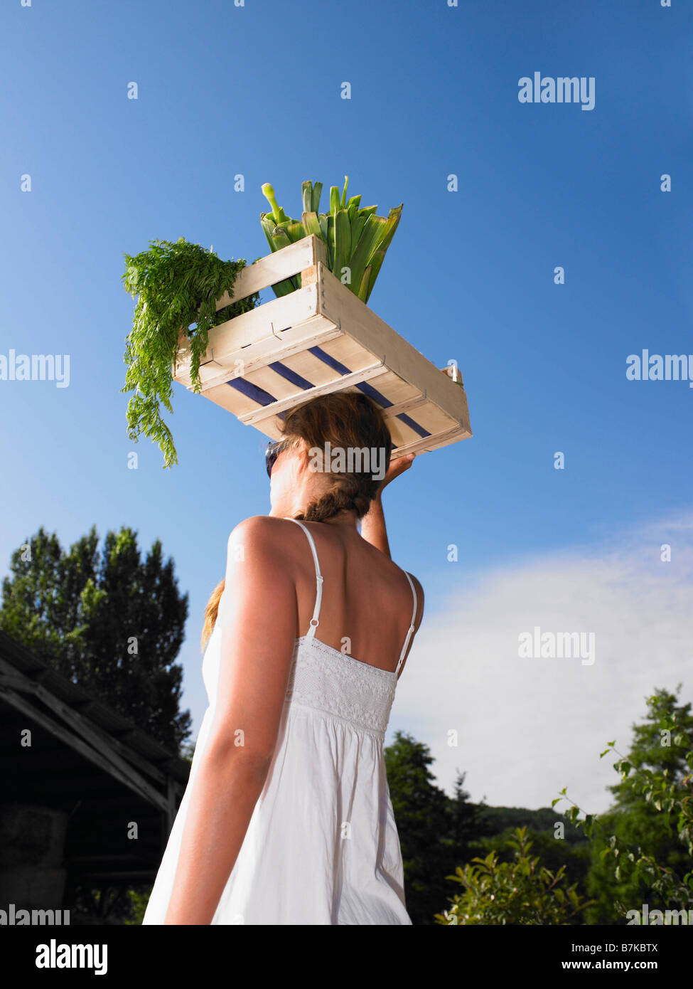 Woman carrying basket of vegetables - Stock Image