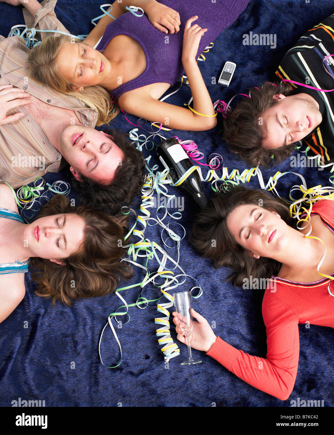 Friends sleeping on floor after party - Stock Image
