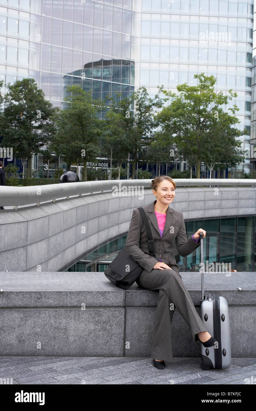 Business woman sitting with luggage - Stock Image