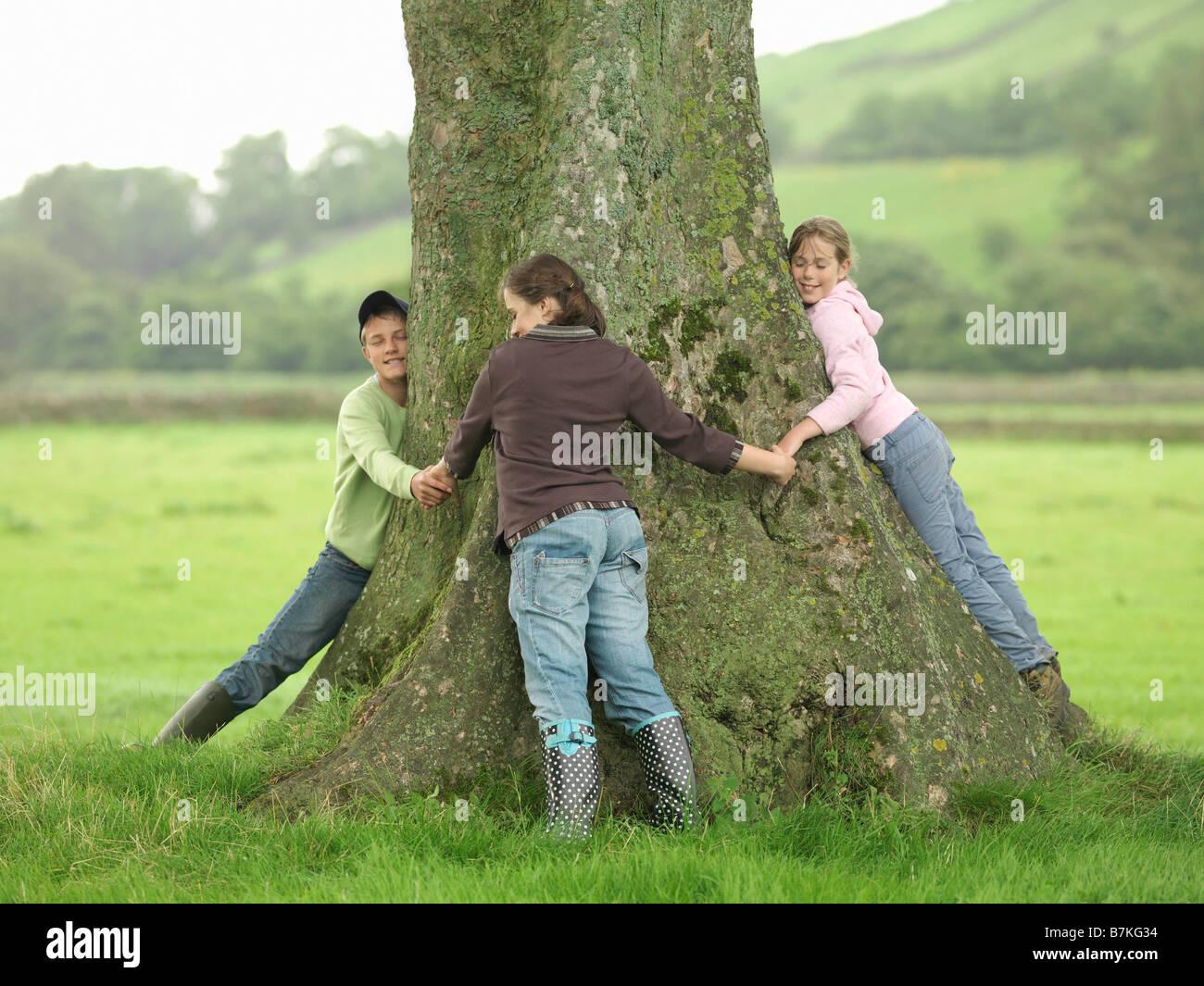 Children Hugging Tree - Stock Image