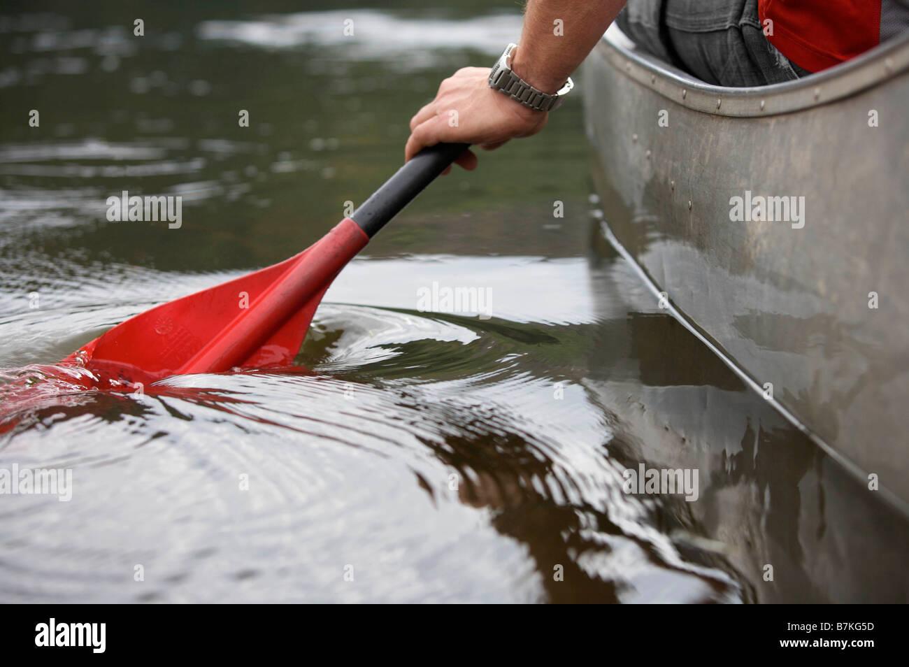 Kayak paddle stroke in water. - Stock Image