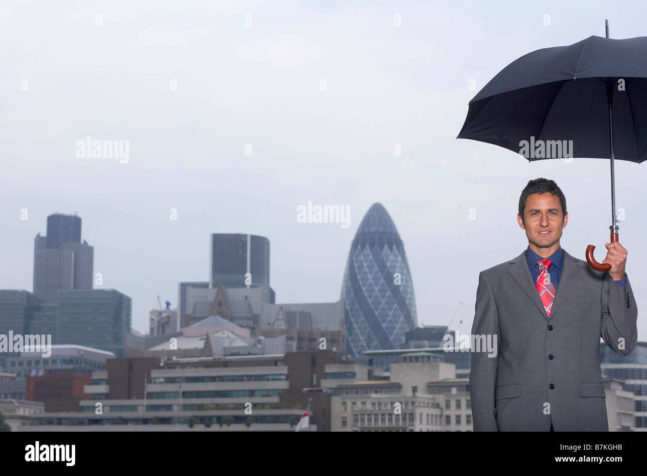 Mann with umbrella city scape - Stock Image