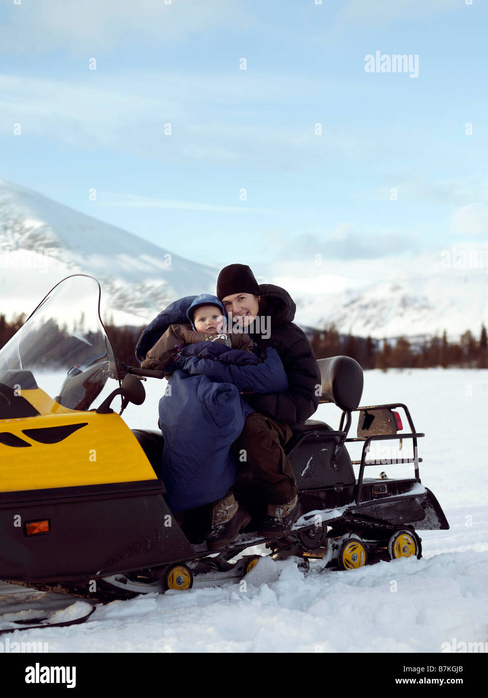 Mother and baby on Snowmobile - Stock Image