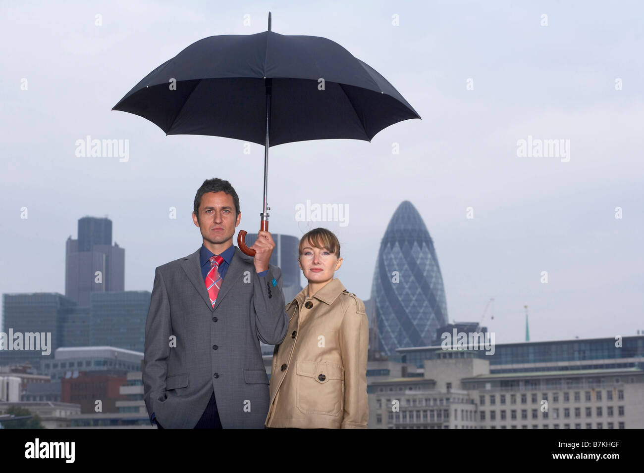 Man & Woman with Umbrella City Scape - Stock Image
