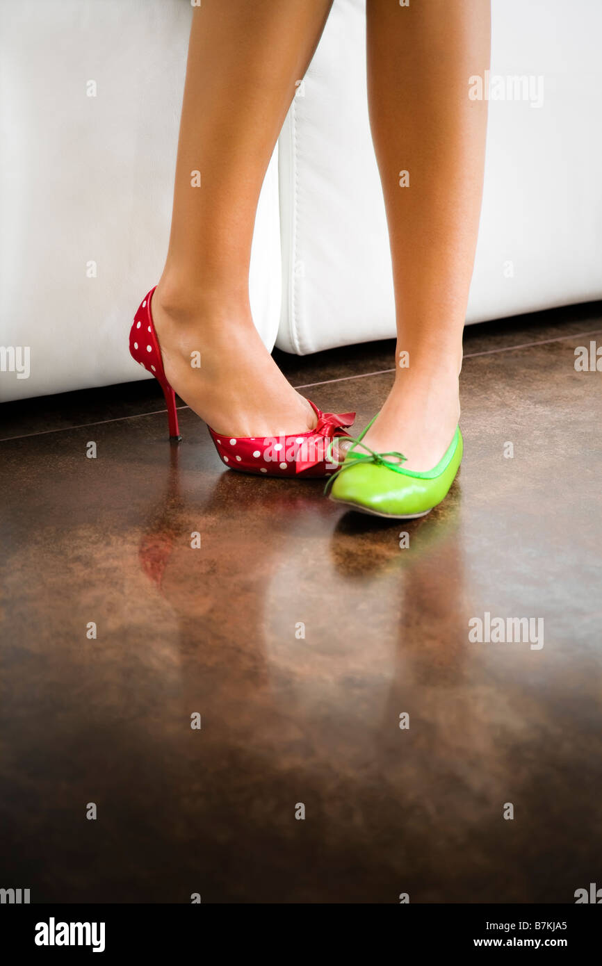 Cropped view of woman wearing mismatched shoes - Stock Image