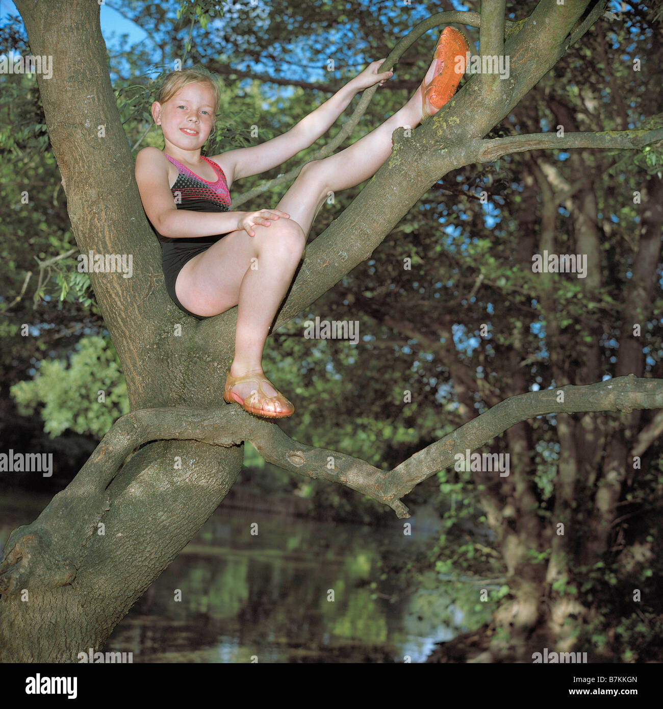 Girl perched in a tree over a river - Stock Image